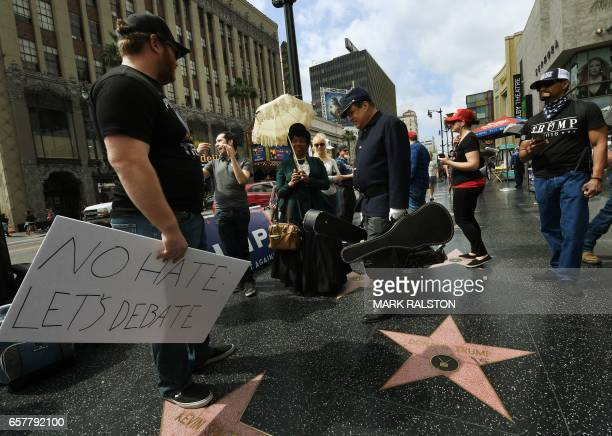 Supporters of US President Donald Trump stand beside his 'Hollywood Walk of Fame' star during the 'Make America Great Again' rally in Hollywood...