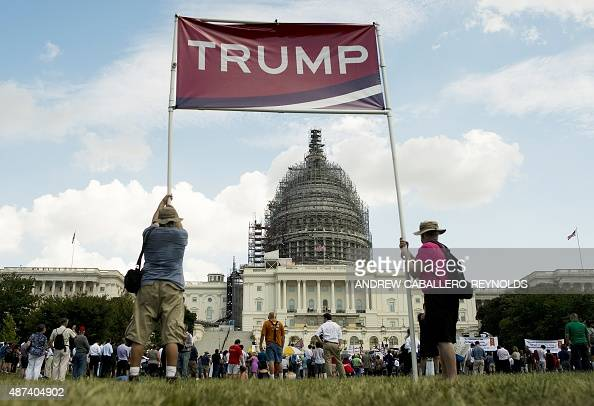 Supporters of US Republican Presidential hopeful Donald Trump hold up a sign during a Tea Party rally against the international nuclear agreement...