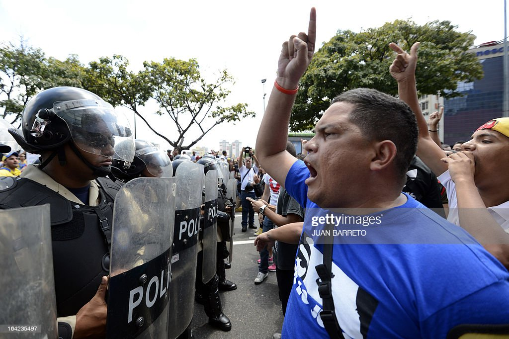 Supporters of Venezuelan acting president Nicolas Maduro shout slogans at opposition students (not depicted) demonstrating in downtown Caracas on March 21, 2013 demanding to the National Electoral Council (CNE) transparency during the presidential elections next February 14.