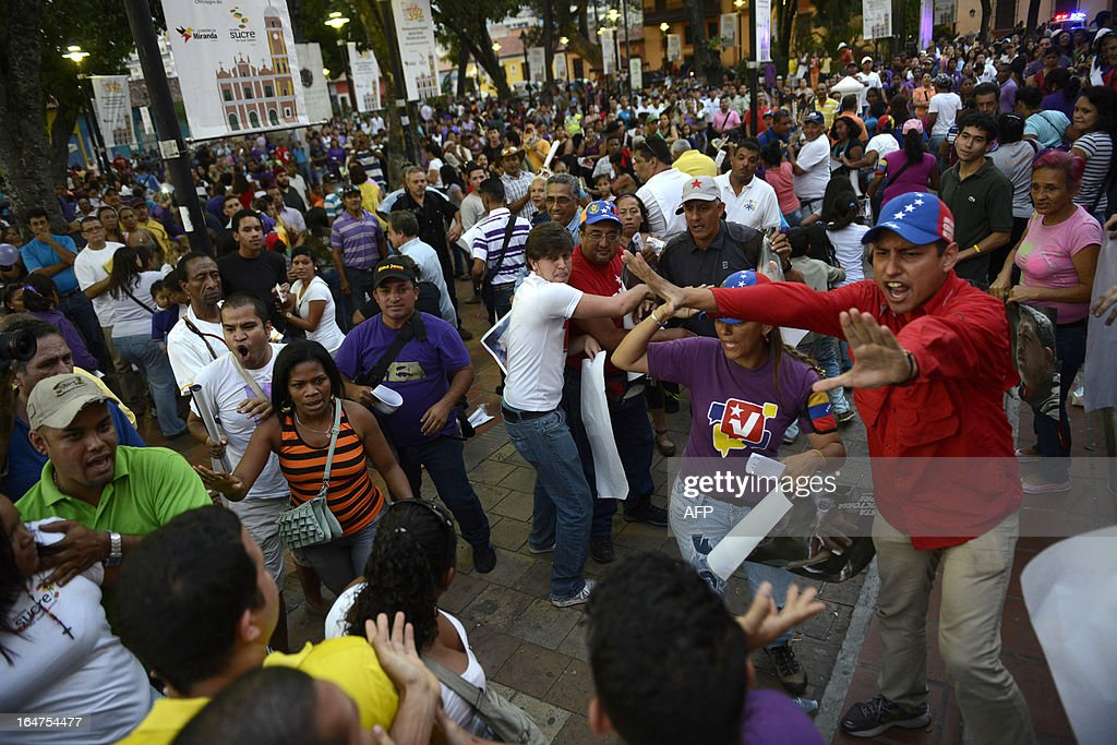 Supporters of Venezuelan former President Hugo Chavez and supporters of opposition presidential candidate Henrique Capriles Radonski confront outside a church after Capriles' arrival in Caracas on March, 27, 2013. AFP PHOTO/Leo RAMIREZ