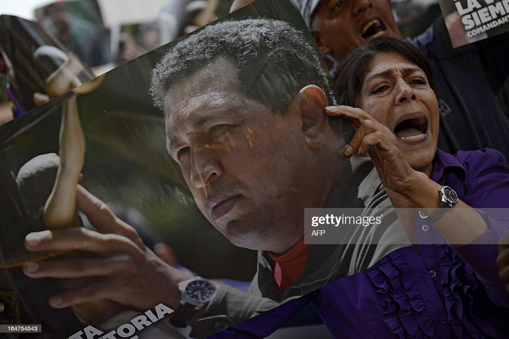 Supporters of Venezuelan former President Hugo Chavez hold posters with his portrait as they shout slogans outside a church where opposition presidential candidate Henrique Capriles Radonski is attending a Holy Week mass in Caracas on March, 27, 2013. AFP PHOTO/Leo RAMIREZ