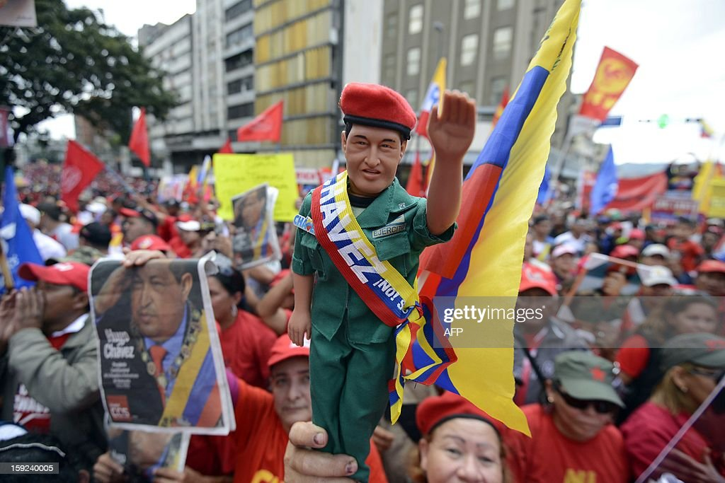 Supporters of Venezuelan President Hugo Chavez gather outside Miraflores presidential palace during an event in homage of Chavez, in Caracas on January 10, 2013. With Chavez ailing and absent, Venezuela's leftist government launches a new presidential term with a display of popular support on the day he was to be inaugurated. The Supreme Court cleared the cancer-stricken president,kwho is recovering from a fourth round of cancer surgery in Havana, to indefinitely postpone his re-inauguration and said his existing administration could remain in office until he is well enough to take the oath. The government has said that he is recovering from complications from surgery, most recently a severe pulmonary infection that had resulted in a 'respiratory insufficiency.' AFP PHOTO/LEO RAMIREZ