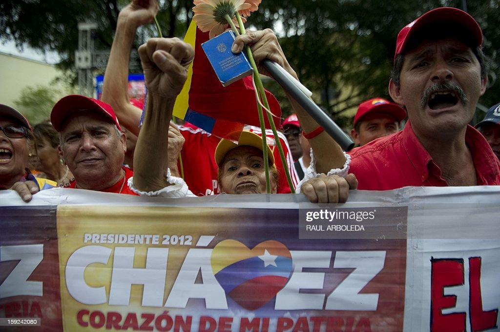 Supporters of Venezuelan President Hugo Chavez gather outside Miraflores presidential palace during an event in homage of Chavez, in Caracas on January 10, 2013. With Chavez ailing and absent, Venezuela's leftist government launches a new presidential term with a display of popular support on the day he was to be inaugurated. The Supreme Court cleared the cancer-stricken president,kwho is recovering from a fourth round of cancer surgery in Havana, to indefinitely postpone his re-inauguration and said his existing administration could remain in office until he is well enough to take the oath. The government has said that he is recovering from complications from surgery, most recently a severe pulmonary infection that had resulted in a 'respiratory insufficiency.' AFP PHOTO/Raul ARBOLEDA