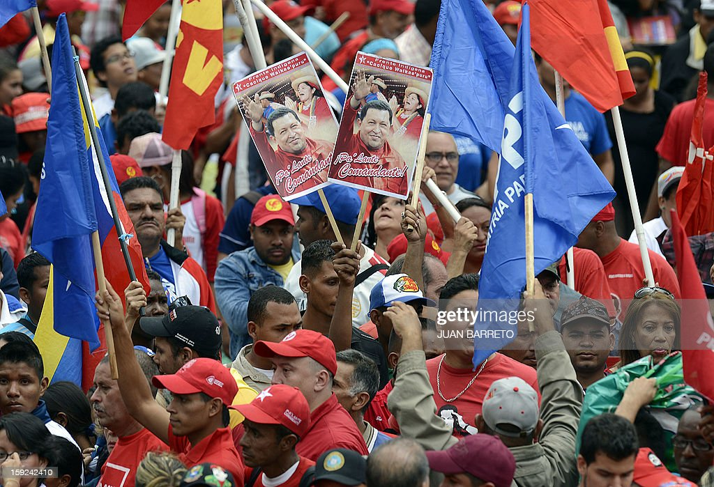 Supporters of Venezuelan President Hugo Chavez gather outside Miraflores presidential palace during an event in homage of Chavez, in Caracas on January 10, 2013. With Chavez ailing and absent, Venezuela's leftist government launches a new presidential term with a display of popular support on the day he was to be inaugurated. The Supreme Court cleared the cancer-stricken president,kwho is recovering from a fourth round of cancer surgery in Havana, to indefinitely postpone his re-inauguration and said his existing administration could remain in office until he is well enough to take the oath. The government has said that he is recovering from complications from surgery, most recently a severe pulmonary infection that had resulted in a 'respiratory insufficiency.' AFP PHOTO/JUAN BARRETO