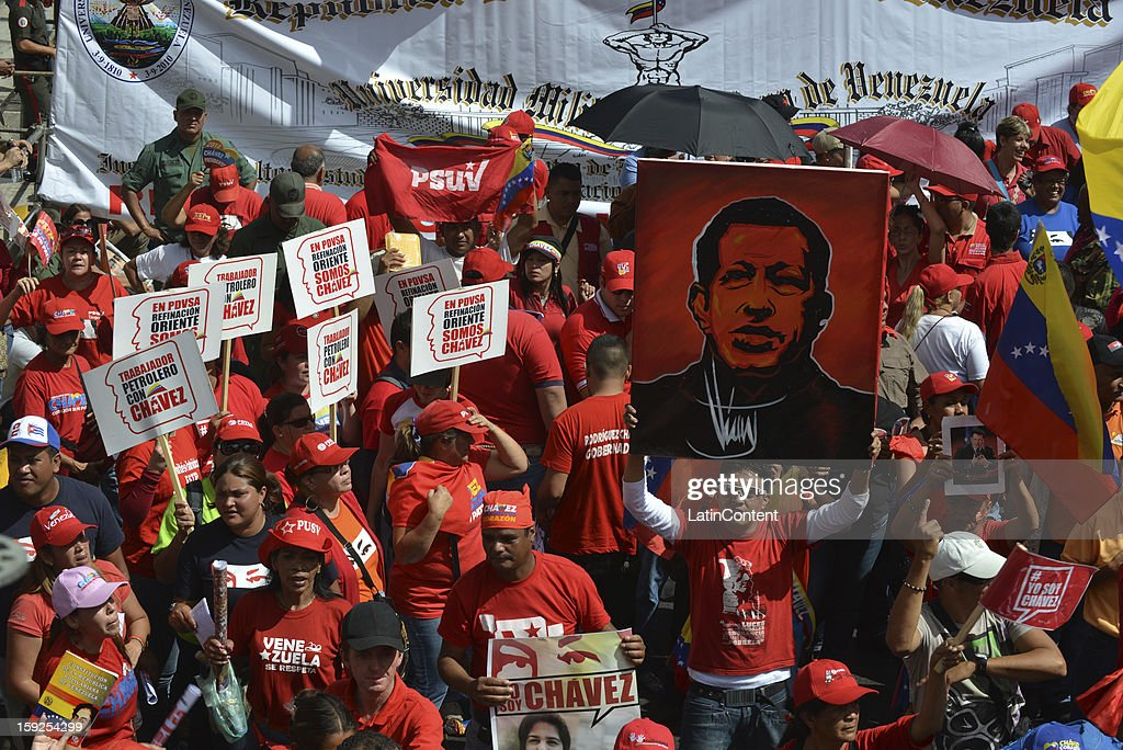 Supporters of Venezuelan President Hugo Chavez hold billboards on January 10, 2013 in Caracas, Venzuela. Chavez is now hospitalized in Cuba due to a cancer. Meanwhile, his followers back him up in the day a new presidential term is inaugurated without him. People make their way to Miraflores Presidential Palace to witness a symbolic swearing-in.
