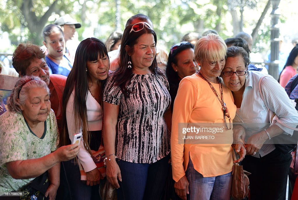 Supporters of Venezuelan President Hugo Chavez look at a TV as pictures of the ailing leader surrounded by his daughters in Havana are released to the public, in Caracas on February 15, 2013. Chavez was seen bed-ridden but smiling in photos released Friday that gave a jittery nation a first glimpse of him since his fourth round of cancer surgery in December. The total of four images -- of Chavez holding Thursday's edition of the official Cuban communist party newspaper Granma -- broke a virtual news blackout for Venezuelans living in a state of limbo without their once media-happy and larger than life comandante.