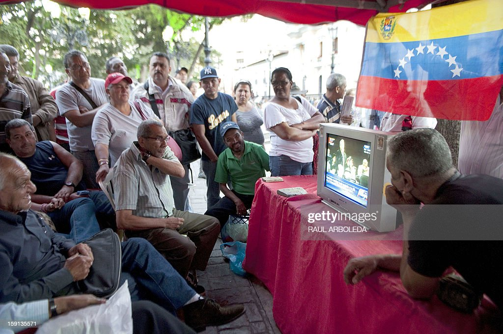 Supporters of Venezuelan President Hugo Chavez lwatch a session of the National Assembly on television in Caracas on January 8, 2013. The President of the National Assembly Diosdado Cabello announced today that due to health reasons, Chavez will not be able to take the oath to be sworn in for a fourth term in office next January 10. A constitutional fight intensified with the government planning a massive show of support in the streets on the day he is supposed to be sworn in. Chavez, who underwent his fourth round of cancer surgery in Havana nearly a month ago, is suffering from a severe pulmonary infection that has resulted in a respiratory insufficiency. AFP PHOTO/Raul ARBOLEDA