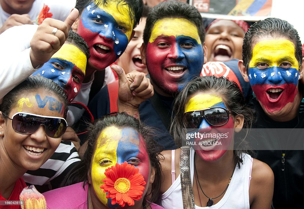 Supporters of Venezuelan President Hugo Chavez pose as they gather outside Miraflores presidential palace during an event in homage of Chavez, in Caracas on January 10, 2013. With Chavez ailing and absent, Venezuela's leftist government launches a new presidential term with a display of popular support on the day he was to be inaugurated. The Supreme Court cleared the cancer-stricken president,kwho is recovering from a fourth round of cancer surgery in Havana, to indefinitely postpone his re-inauguration and said his existing administration could remain in office until he is well enough to take the oath. The government has said that he is recovering from complications from surgery, most recently a severe pulmonary infection that had resulted in a 'respiratory insufficiency.' AFP PHOTO/Raul ARBOLEDA