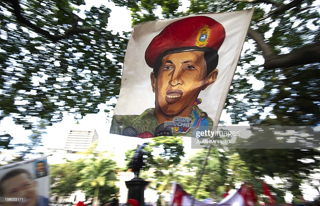 Supporters of Venezuelan President Hugo Chavez wave a flag with his image during a rally in Caracas on December 9, 2012. Chavez was poised to head to Cuba Sunday for more cancer surgery, after speaking for the first time of a successor in this oil-rich nation he so thoroughly dominates should he not recover. Treatment is 'absolutely necessary,' the leftist leader said in a bombshell statement on state television in which he admitted he may have to give up the presidency and that Vice President Nicolas Maduro is his chosen successor. AFP PHOTO