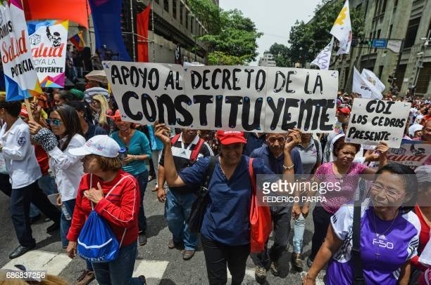 Supporters of Venezuelan President Nicolas Maduro hold a banner reading 'In support of the decree of the constituent' referring to the constituent...