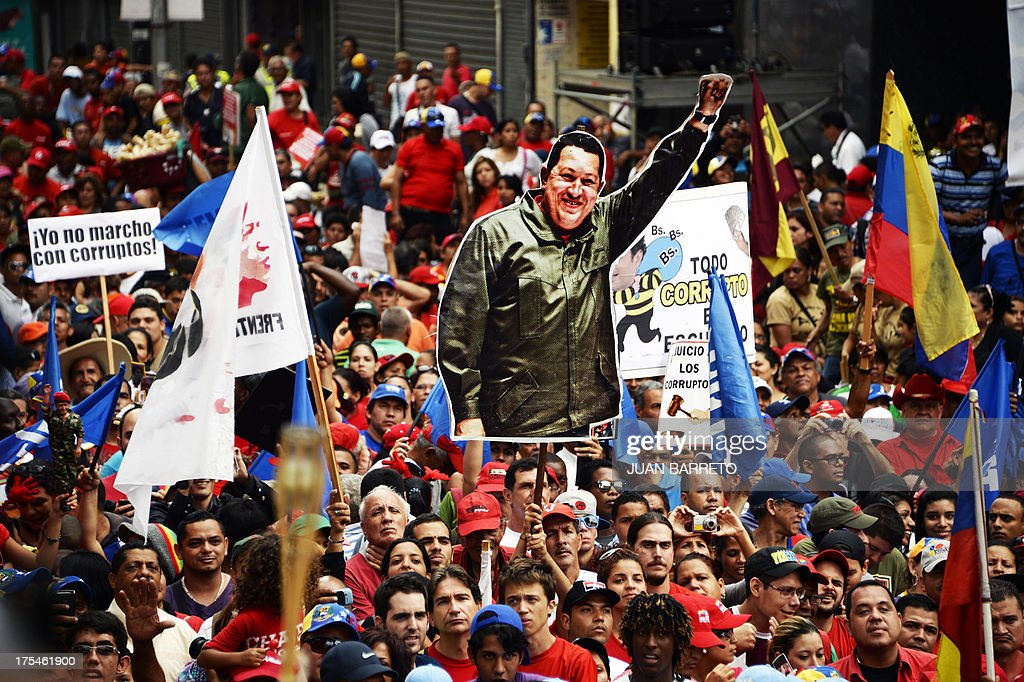 Supporters of Venezuelan President Nicolas Maduro hold a poster of former Venezuelan President Hugo Chavez (1954-2013) during a demonstration in Caracas on August 3, 2013. Maduro and opposition leader Henrique Capriles leaded Saturday simultaneous demos against corruption. AFP PHOTO