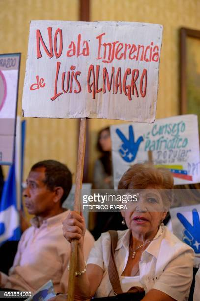 Supporters of Venezuelan President Nicolas Maduro hold posters against the secretary general of the Organization of American States Luis Almagro as...