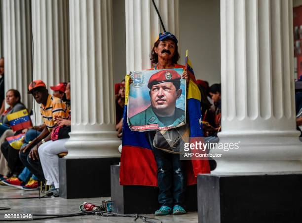 Supporters of Venezuelan president Nicolas Maduro holds a photo of the deceased former president Hugo Chavez in the National Assembly in Caracas on...