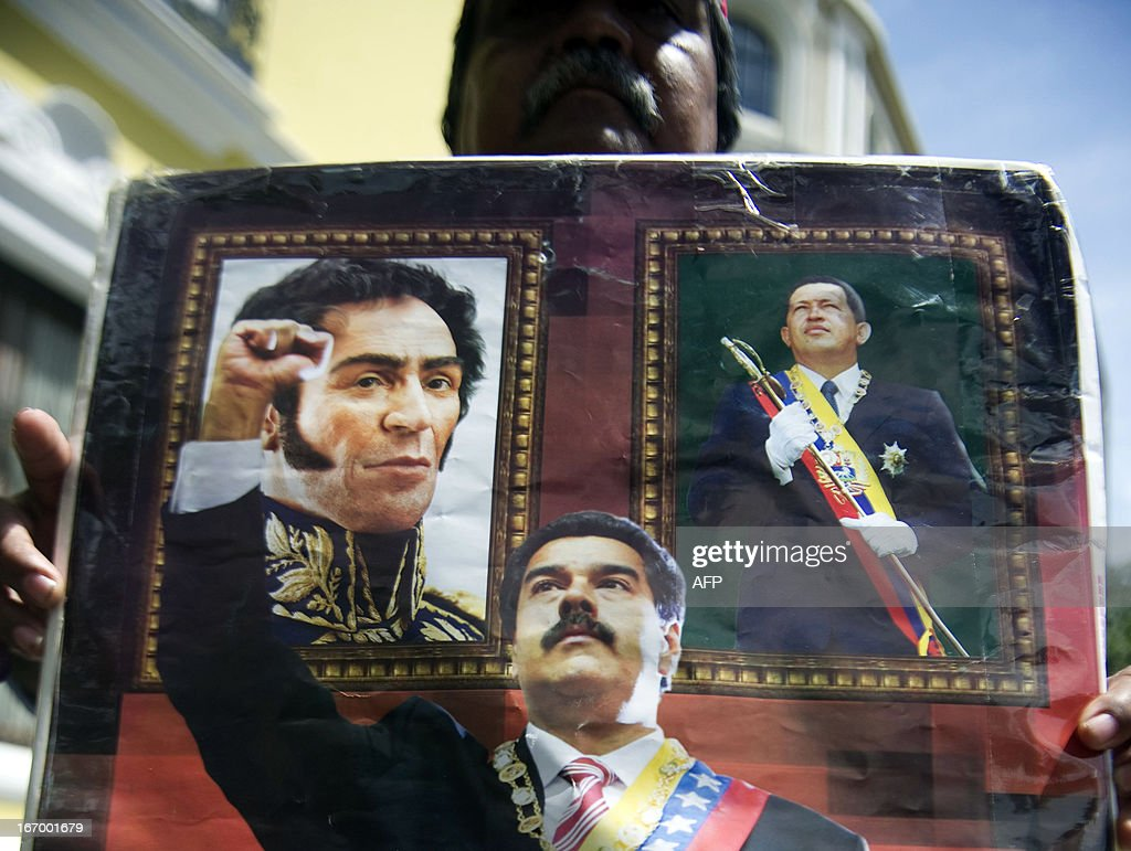 Supporters of Venezuelan President Nicolas Maduro show images of late President Hugo Chavez (R), national hero Simon Bolivar (L) and Maduro when they gather in front of the National Assembly before the inauguration ceremony of Maduro, in Caracas on April 19, 2013. Maduro was set to be inaugurated in Venezuela Friday, even as election officials moved to defuse a political crisis by yielding to demands for an audit of the results in Sunday's bitterly contested elections. The last minute development came after Maduro flew to a South American summit in Peru Thursday, where he received international support for his new government hours before he was to be sworn in to succeed the late Hugo Chavez who died of cancer March 5. AFP PHOTO/Raul ARBOLEDA