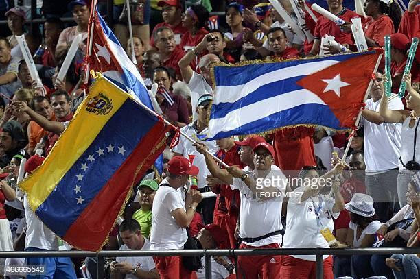 Supporters of Venezuela's Navegantes del Magallanes and Cuba's Azucareros de Villa Clara wave flags during their 2014 Caribbean baseball series game...