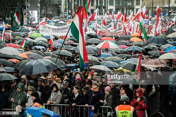 Supporters of Viktor Orban Hungary's prime minister shelter under umbrellas during an official address outside the National Museum of Hungary in...