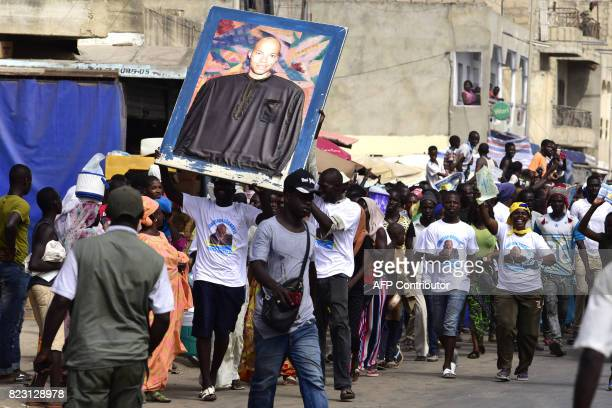 Supporters of Wattu Senegal coalition candidate and former president Abdoulaye Wade shout slogans while holding a portrait of his son Karim Wade...