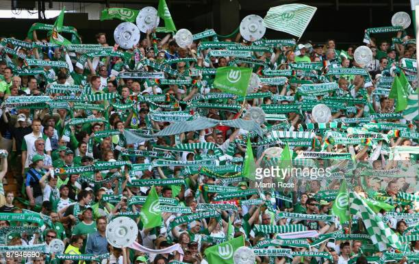 Supporters of Wolfsburg celebrate the German championship with the trophy after their Bundesliga match against SV Werder Bremen on May 23 2009 in...
