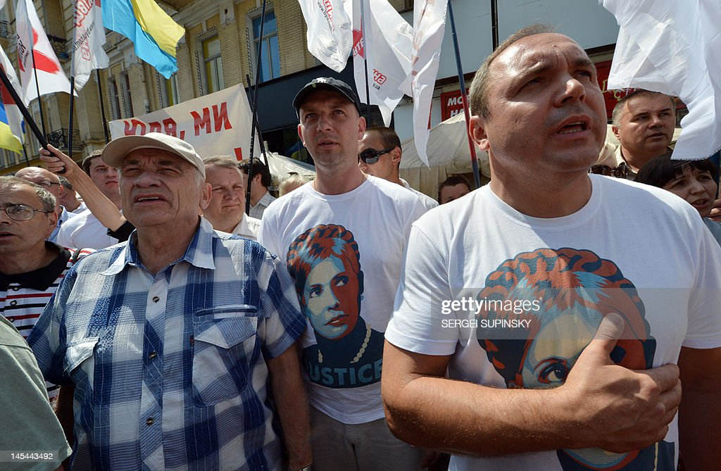 Supporters of Yulia Tymoshenko wearing t-shirts depicting her portrait sing the Ukrainian anthem during a rally in the camp of the supporters in Kiev on May 30, 2012, as they mark 300 days since the leader of the opposition was jailed. Ukraine's general prosecutor said Wednesday the jailed ex-premier Yulia Tymoshenko was cited as a witness in the murder of a deputy, putting fresh pressure on President Viktor Yanukovych's arch-enemy.