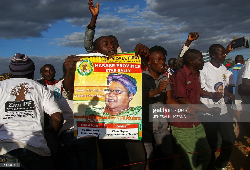 Supporters of Zimbabwe People First (ZPF) cheer their party president Joice Mujuru during the party's first rally in the capital Harare, on June 25 2016. / AFP / Jekesai Njikizana