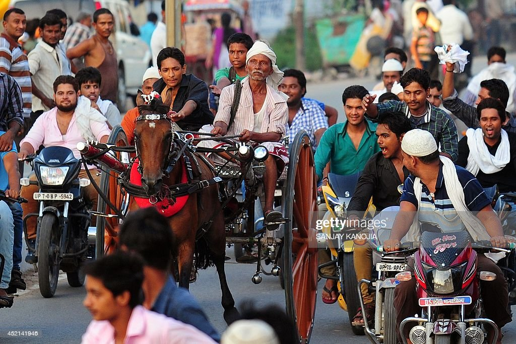 Supporters on motorcycles cheer as Indian participants ride in the 'Ekka' race in Allahabad on July 14 2014 The annual race takes place during the...
