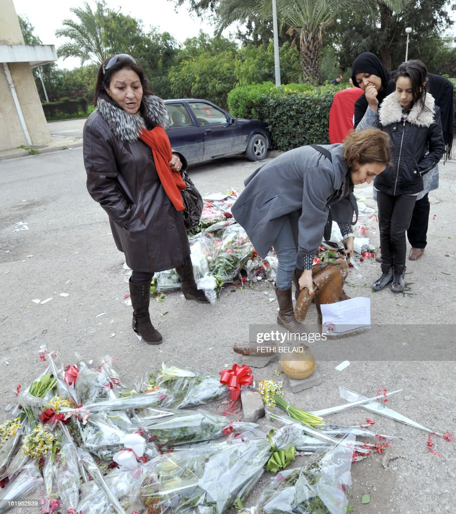Supporters pick-up a piece of the broken statue erected in honour of murdered opposition figure Chokri Belaid, on February 18, 2013, in Tunis. The memorial, installed as a work of contemporary art by Tunisian artists, was ripped off from its base and broken, and the flowers surrounding it were trampled and scattered. Belaid, a leftist leader and fierce critic of Tunisia's ruling Islamist-led government, was shot dead by a gunman as he left his home.