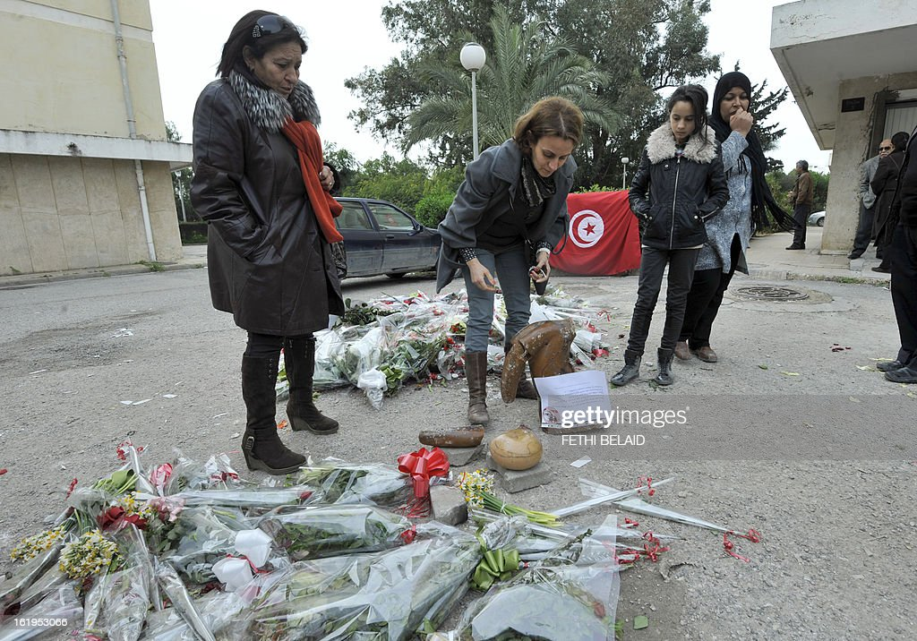 Supporters pick-up the pieces of the broken statue erected in honour of murdered opposition figure Chokri Belaid, on February 18, 2013, in Tunis. The memorial, installed as a work of contemporary art by Tunisian artists, was ripped off from its base and broken, and the flowers surrounding it were trampled and scattered. Belaid, a leftist leader and fierce critic of Tunisia's ruling Islamist-led government, was shot dead by a gunman as he left his home.