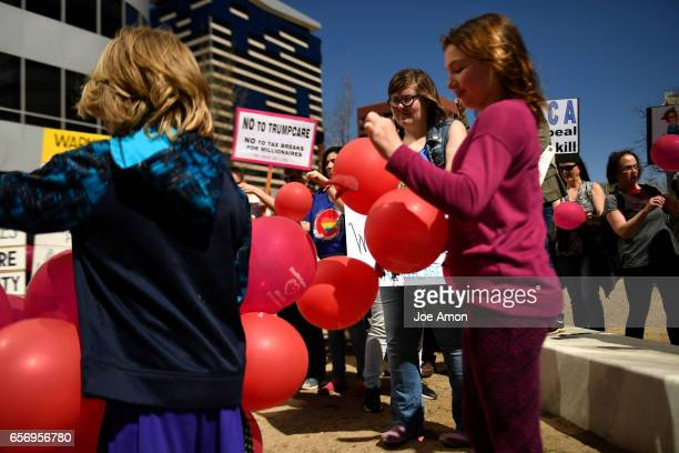 Supporters popping their balloons on the 7th anniversary of the day the Affordable Care Act was signed into law volunteer supporters with the Protect...