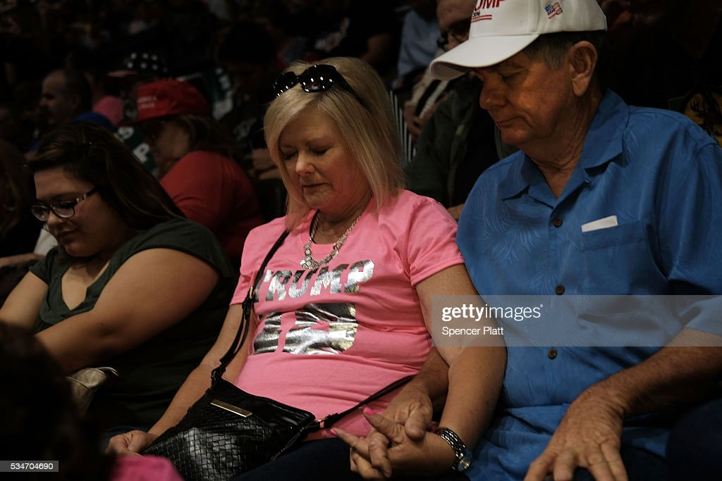 Supporters pray as they wait for the presumtive Republican presidential candidate Donald Trump to speak at a rally in Fresno on May 27, 2016 in Fresno, California. Trump is on a Western campaign trip which saw stops in North Dakota and Montana yesterday and two more in California today.
