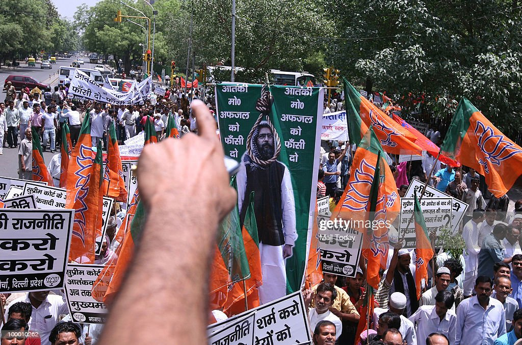 BJP supporters raise party flags and banners in protest against the delay in hanging of Afzal Guru in New Delhi on May 19, 2010.
