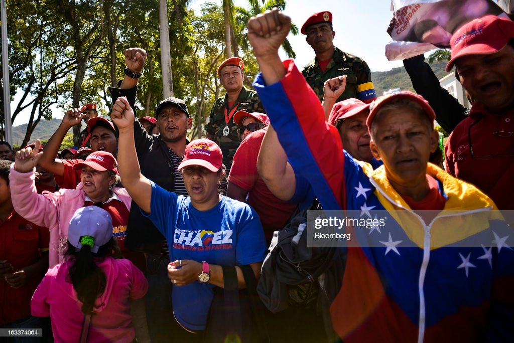 Supporters raise their fists while chanting during the funeral for Venezuelan President Hugo Chavez in Caracas, Venezuela, on Friday, March 8, 2013. Allies of Venezuela's Hugo Chavez paid their final respects to the firebrand socialist leader at a state funeral that marked the emotional high point of a week of tributes preceding a snap election to choose his successor. Photographer: Meridith Kohut/Bloomberg via Getty Images