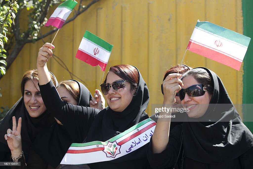 Supporters raise up iranian flag as President Hassan Rouhani of Iran as his motorcade leaves Mehrabad Airport on September 28, 2013 in Tehran, Iran. Hardline Islamists gathered outside the airport to chant ''Death to America'' and ''Death to Israel'' but they were outnumbered by supporters of President Rouhani who shouted 'Thank you Rouhani.' Iranian newspapers hailed the first contact between presidents Rouhani and Obama but warned that Israel would seek to impede the historic opening to Washington.
