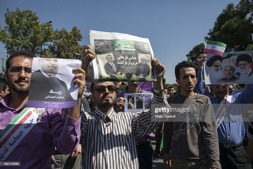Supporters raise up posters depicting President Hassan Rouhani of Iran as his motorcade leaves Mehrabad Airport on September 28, 2013 in Tehran, Iran. Hardline Islamists gathered outside the airport to chant ''Death to America'' and ''Death to Israel'' but they were outnumbered by supporters of President Rouhani who shouted 'Thank you Rouhani.' Iranian newspapers hailed the first contact between presidents Rouhani and Obama but warned that Israel would seek to impede the historic opening to Washington.