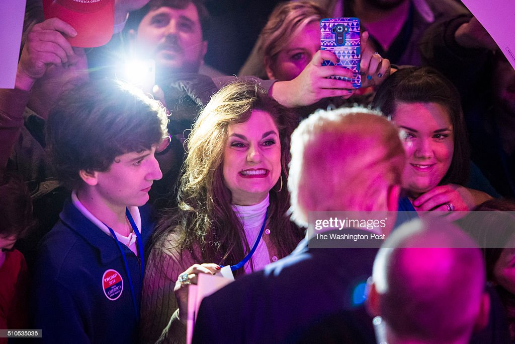 Supporters reach out for signatures handshakes and photos as republican presidential candidate Donald Trump greets the crowd after speaking at a...