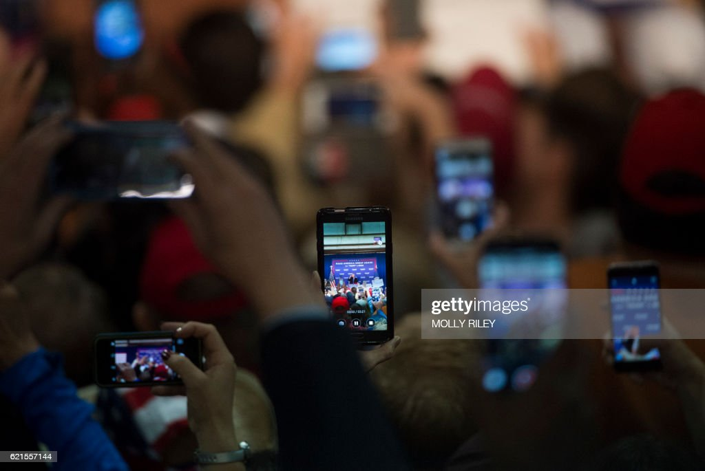 TOPSHOT - Supporters record on their phones as Republican presidential candidate Donald Trump addresses a campaign rally after midnight, early November 7, 2016 at Loudoun Fairgrounds in Leesburg, Virginia. / AFP / MOLLY