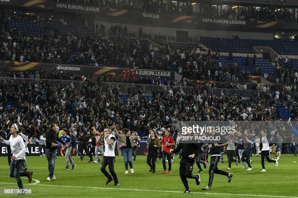Supporters run after entering the pitch before the UEFA Europa League first leg quarter final football match between Lyon and Besiktas on April 13 at...