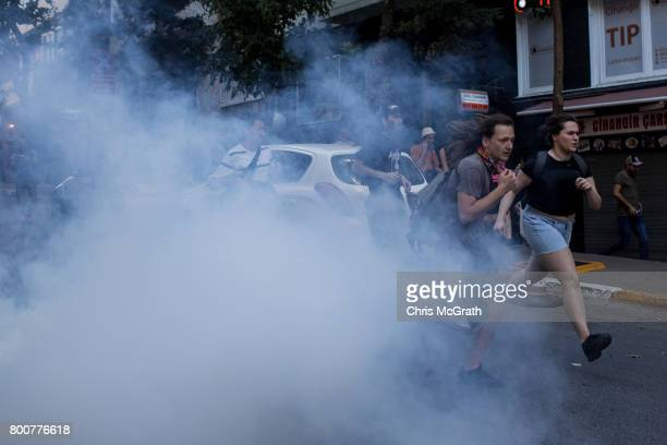 LGBT supporters run from tear gas fired by police after attempting to march to Taksim Square on June 25 2017 in Istanbul Turkey The 2017 LGBT Pride...