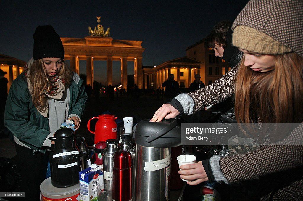 Supporters serve themselves tea on the seventh day of a hunger strike by demonstrating refugees in front of the Brandenburg Gate on October 31, 2012 in Berlin, Germany. The refugees, predominantly from Iran, Afghanistan and Iraq, are subsisting on only water, tea and coffee without sugar. Despite the cold temperatures they have been forbidden by the police from having blankets, tents, or isomattresses, as the possession of which would change the official status of the protest, registered in advance, from a 'demonstration' to a 'camp'. They have been sitting in front of the Brandenburg Gate since October 24 and say they will continue their strike until the German government responds to their demands for a halt to deportations and faster processing of asylum applications. Meanwhile the police have been criticized by local party-affiliated as well as non-partisan activist groups for their restrictions.