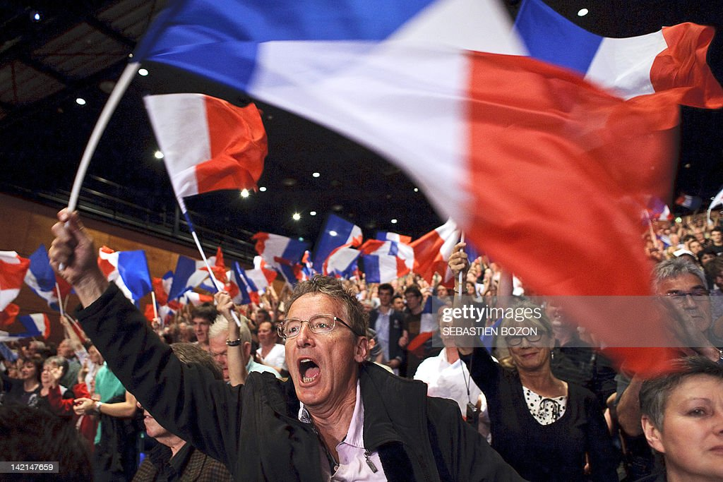 Supporters shout slogans and wave the French national flag as they listen to France's incumbent President and Union for a Popular Movement party...