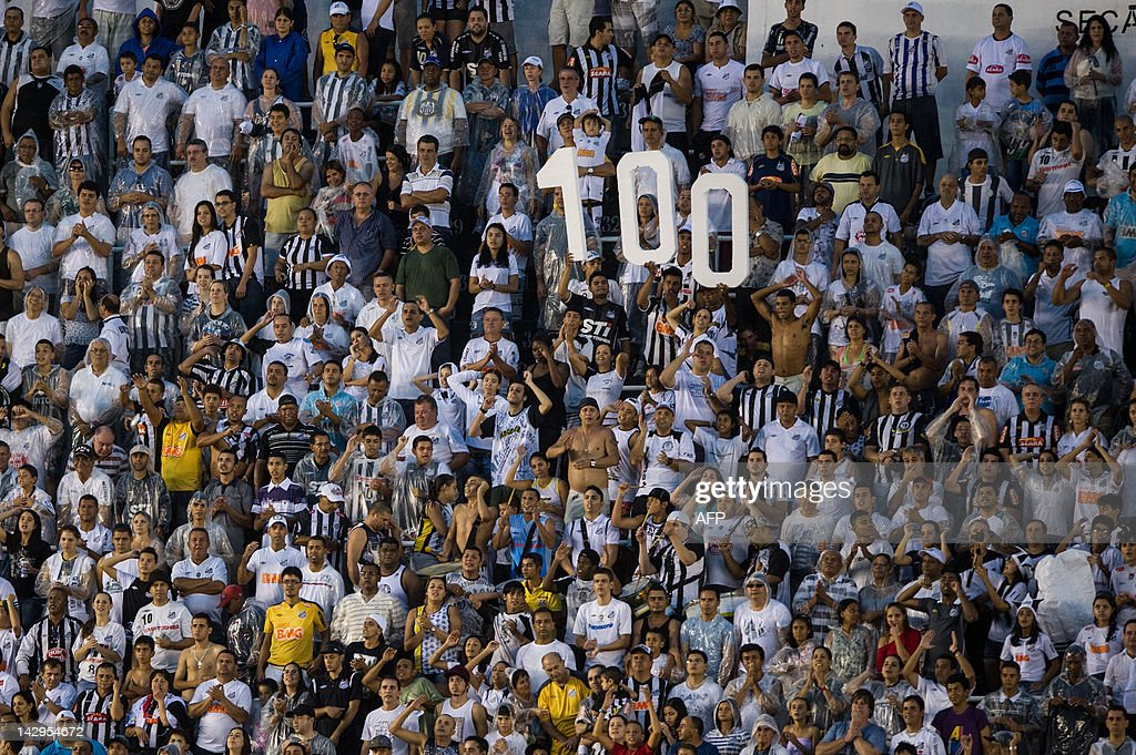 Supporters show the number 100 to celebrate the 100 anniversary of Santos football club during the Paulista Championship football match between...