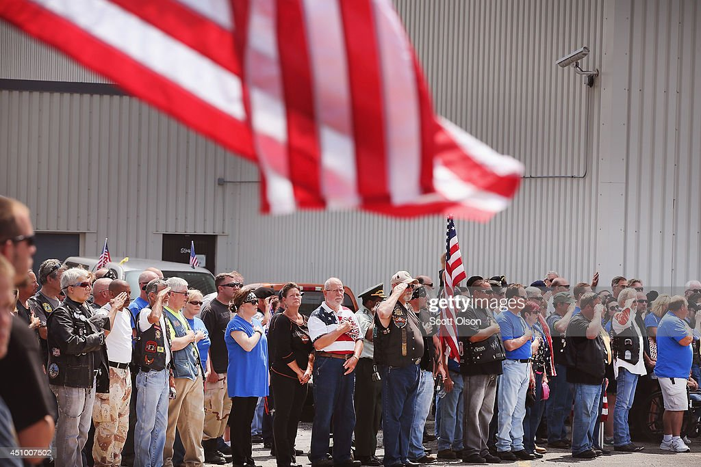Supporters show their respect as the family of Pfc. Aaron Toppen arrive at Midway Airport to claim his remains on June 21, 2014 in Chicago, Illinois. Toppen, 19, was killed alongside four other American Soldiers and an Afghan soldier in a friendly fire airstrike during a firefight earlier this month in Afghanistan.