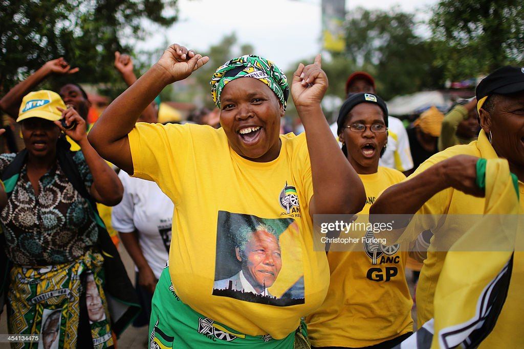 ANC supporters sing and dance to celebrate the life of Nelson Mandela outside his former home in Viliakazi Street, Soweto Township, on December 7, 2013 in Soweto, South Africa. Mandela, also known as Tata Madiba, passed away on the evening of December 5th at his home in Houghton at the age of 95. Mandela became South Africa's first black president after being jailed for decades for his activism against apartheid in a racially-divided South Africa.