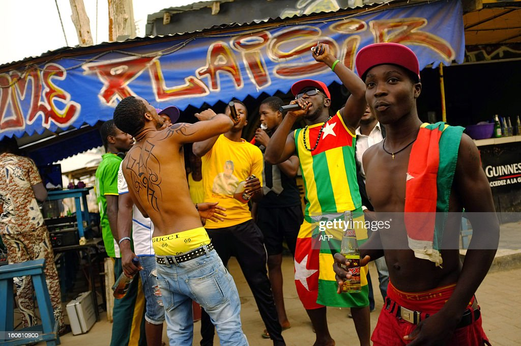 Supporters sing on February 3, 2013 at a bar in Lome before watching the African Cup of Nation 2013 quarter final football match between Burkina Faso and Togo, later today in Nelspruit, South Africa. AFP PHOTO / Daniel Hayduk