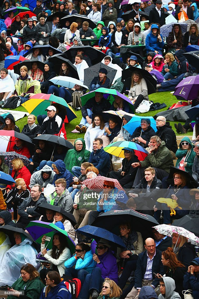 Supporters sit on Murray mound as they take cover from the rain on day three of the Wimbledon Lawn Tennis Championships at the All England Lawn Tennis and Croquet Club on June 29, 2016 in London, England.