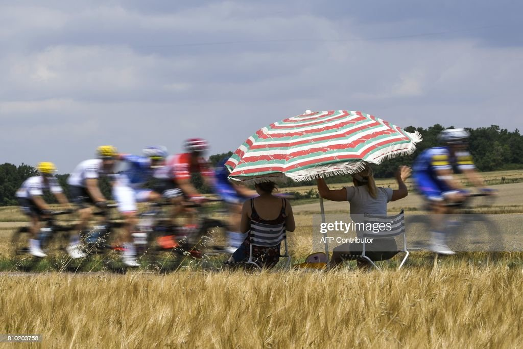 Supporters sitting under a parasol look at the pack riding during the 213,5 km seventh stage of the 104th edition of the Tour de France cycling race on July 7, 2017 between Troyes and Nuits-Saint-Georges. / AFP PHOTO / Lionel BONAVENTURE