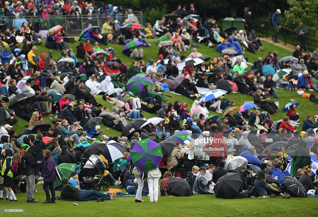 Supporters stand on Murray mound as they take cover from the rain on day three of the Wimbledon Lawn Tennis Championships at the All England Lawn Tennis and Croquet Club on June 29, 2016 in London, England.
