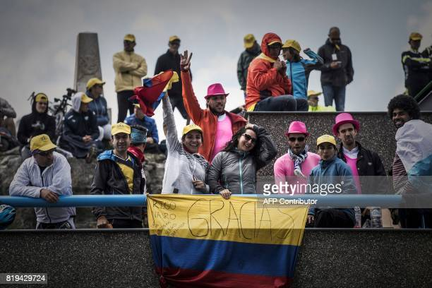 Supporters standing behind a flag of Colombia cherring Colombia's Rigoberto Uran wait for riders at the Col d'Izoard near the finish line during the...