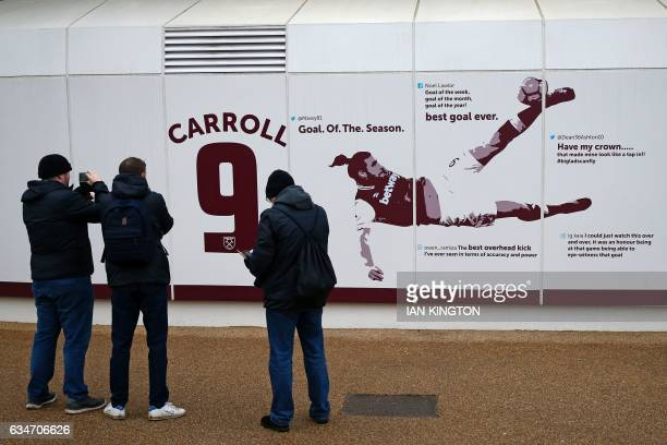 Supporters take pictures of the new mural of Andy Carroll's wonder goal against Crystal Palace on the outside of the stadium ahead of the English...