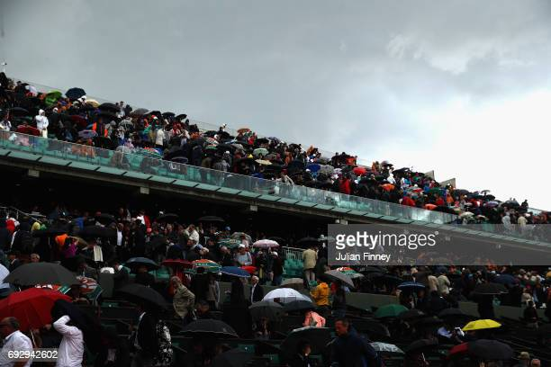 Supporters take shelter from the rain on Court Philippe Chatrier as Kristina Mladenovic of France and Timea Bacsinszky of Switzerland play in the...
