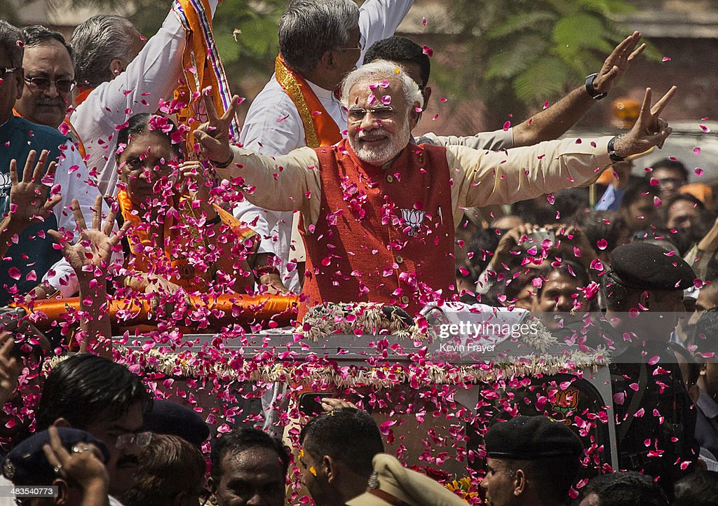Supporters throw flower petals as Bharatiya Janata Party (BJP) leader <a gi-track='captionPersonalityLinkClicked' href=/galleries/search?phrase=Narendra+Modi&family=editorial&specificpeople=822611 ng-click='$event.stopPropagation()'>Narendra Modi</a> rides in an open jeep on his way to file nomination papers on April 9, 2014 in Vadodra, India. India is in the midst of a nine-phase election from April 7-May 12.